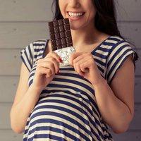 Schwangere Frau mit einer Tafel Schokolade
